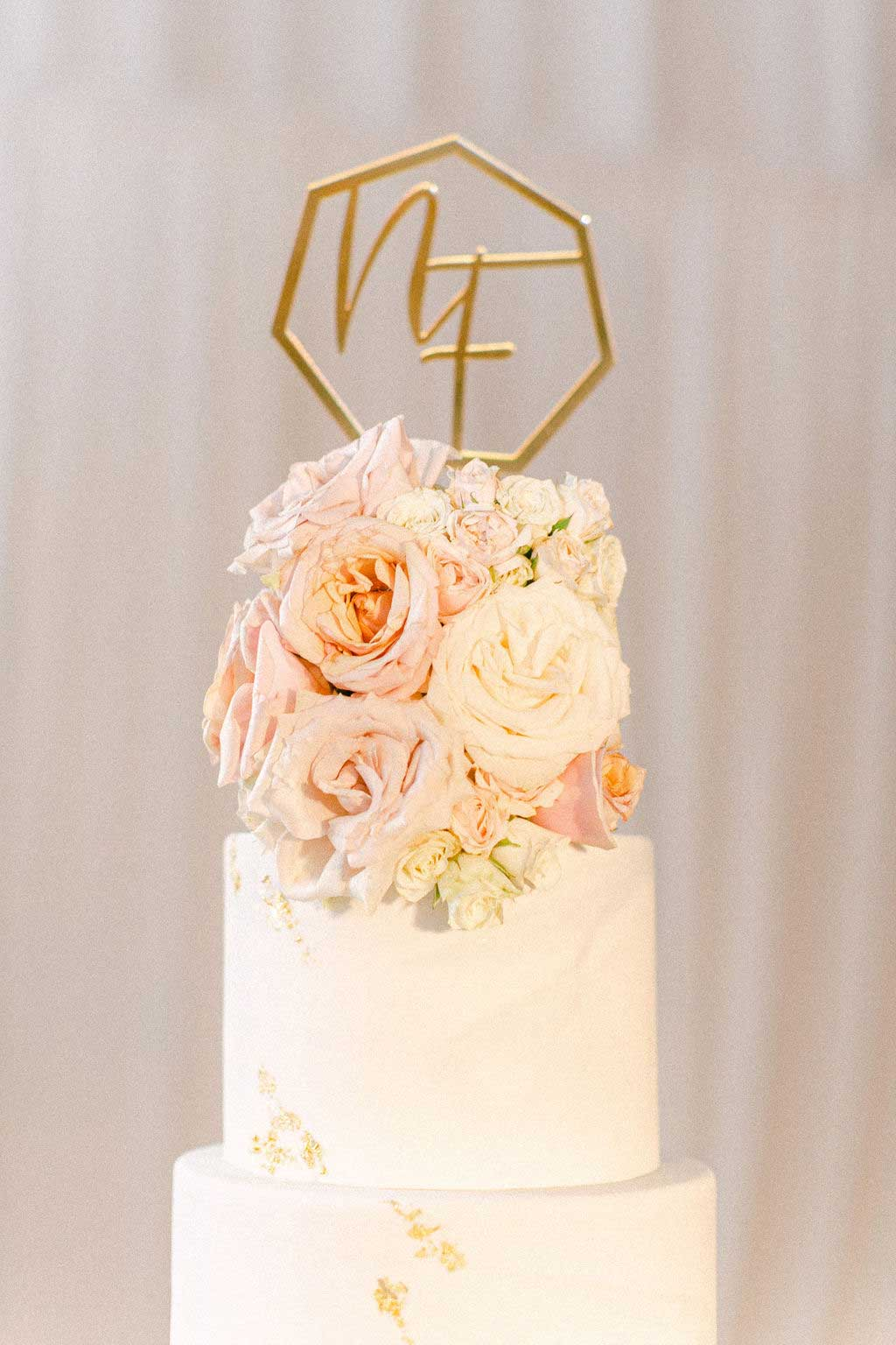 Closeup of wedding cake with floral cake topper and gold initials.