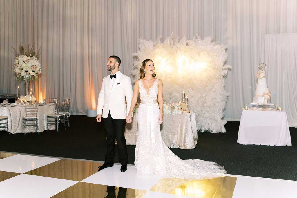 Ballroom reveal with gold and white dance floor and feather wall with gold sign.
