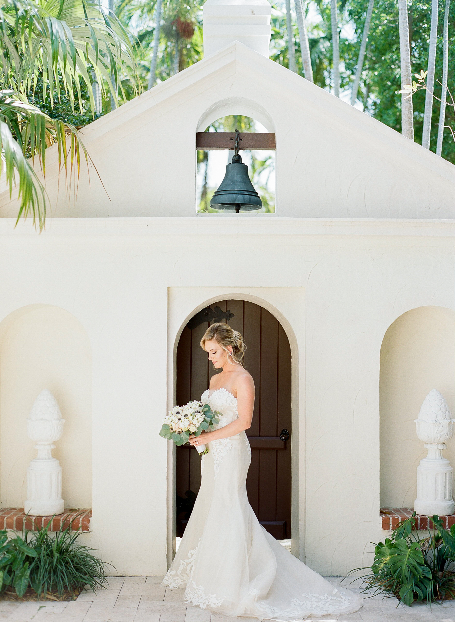 Bride stands in front of door and looks down at her bouquet wearing a strapless gown.