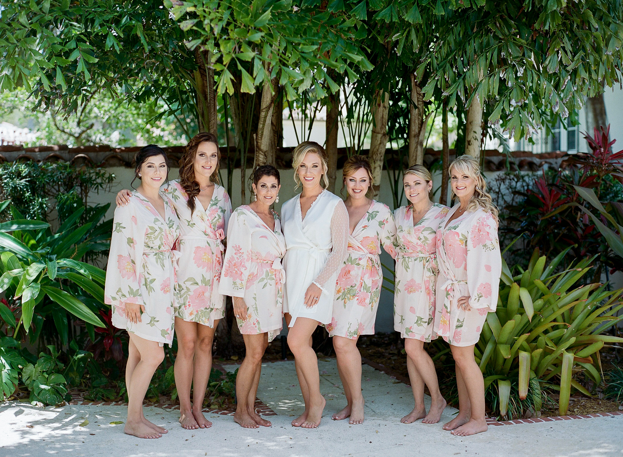 Bride stands and smiles outside with bridal party in their matching blush and floral robes.