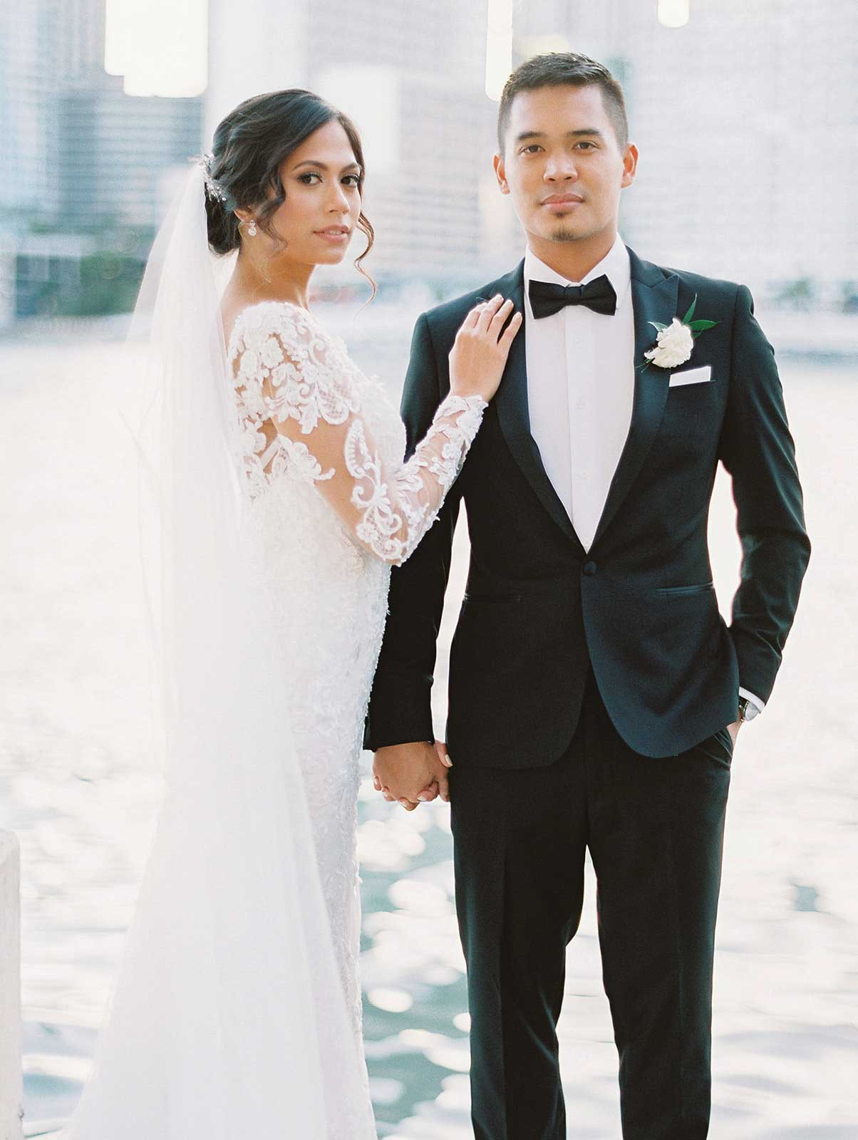 bride and groom stand in front of the Miami River for their couple portrait.