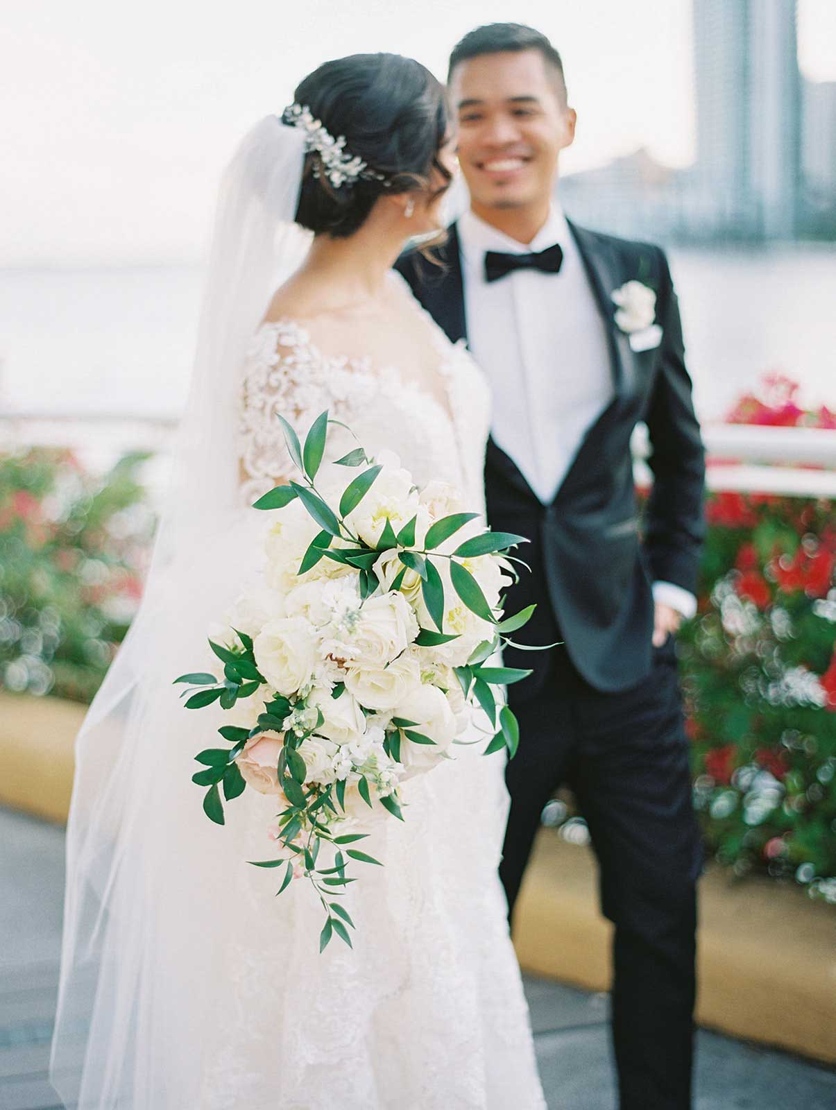 side angle of bride and groom walking towards the camera smiling at each other with bride holding her bouquet.