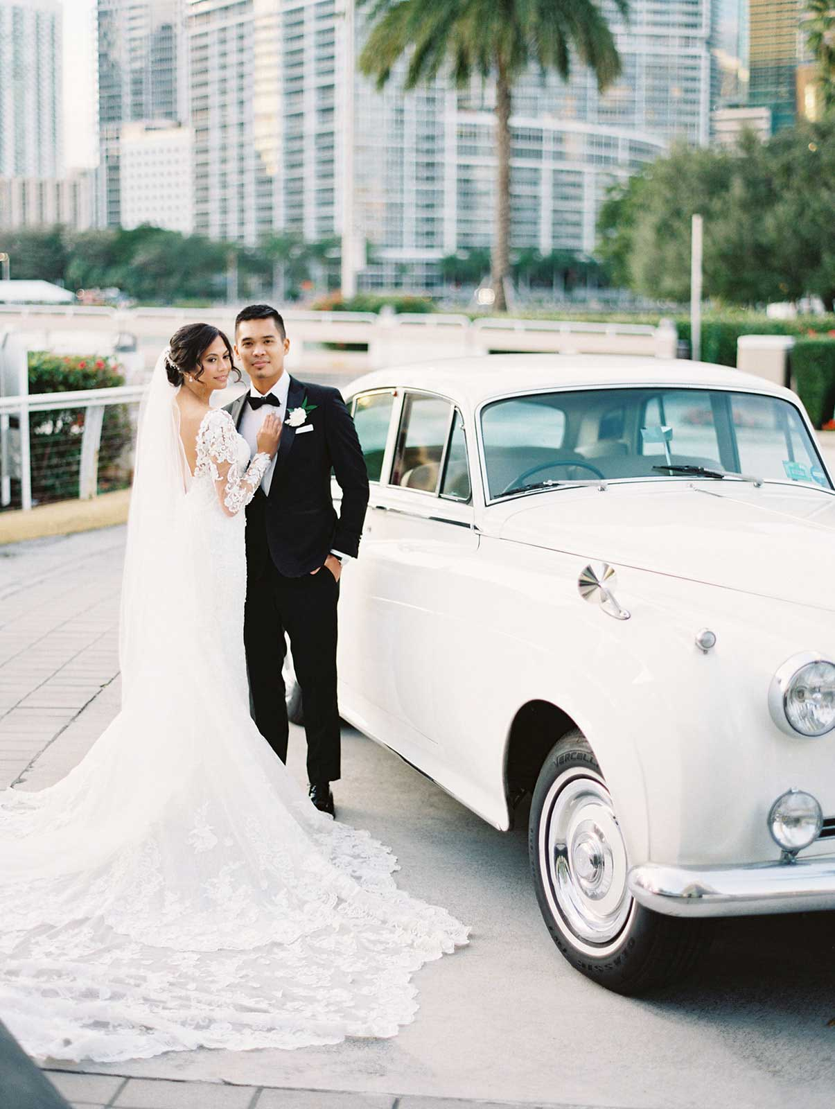 bride and groom stand outside the Epic in front of their white car.