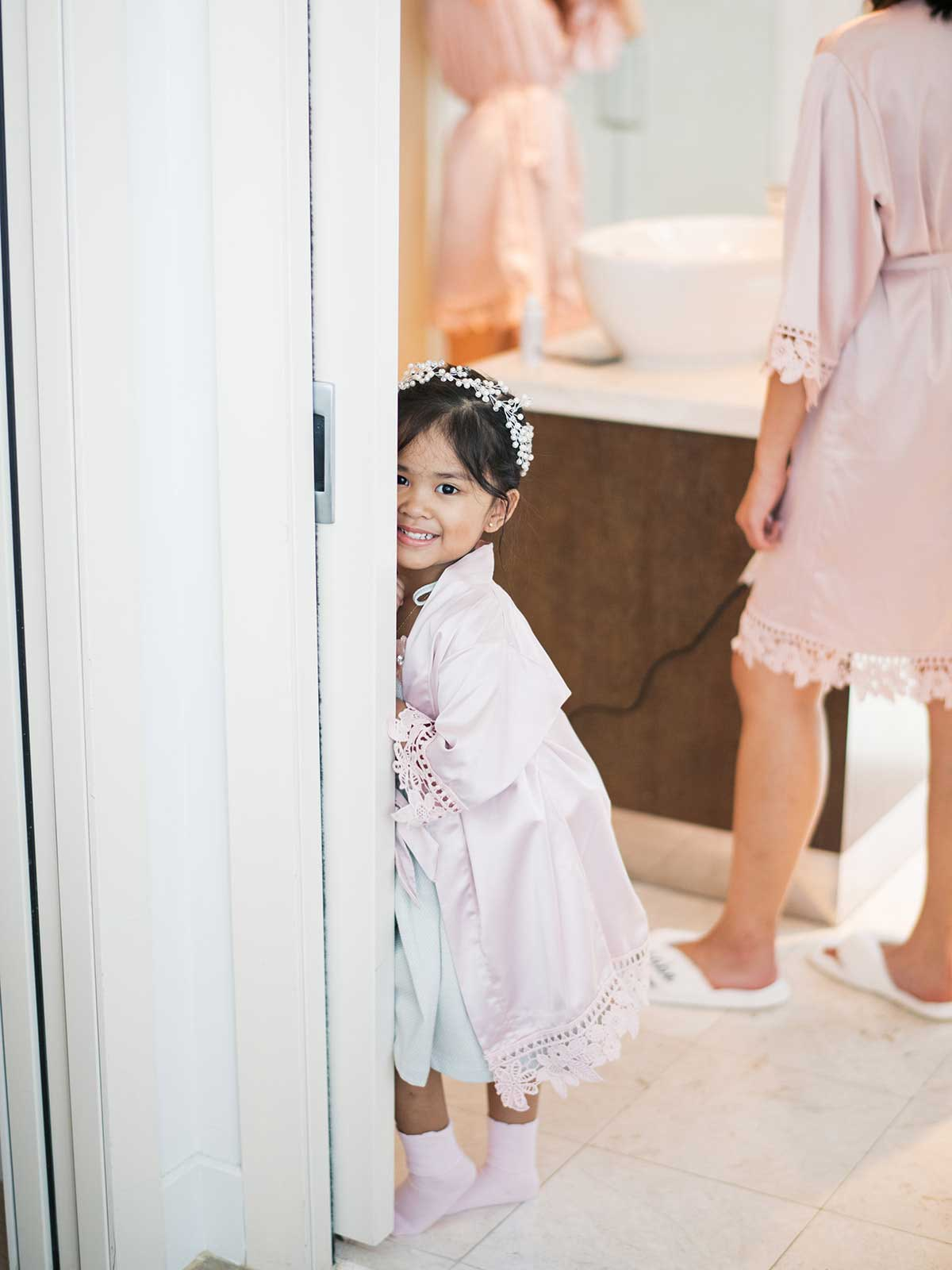 flower girl stands and smiles near door with her robe and flower crown.