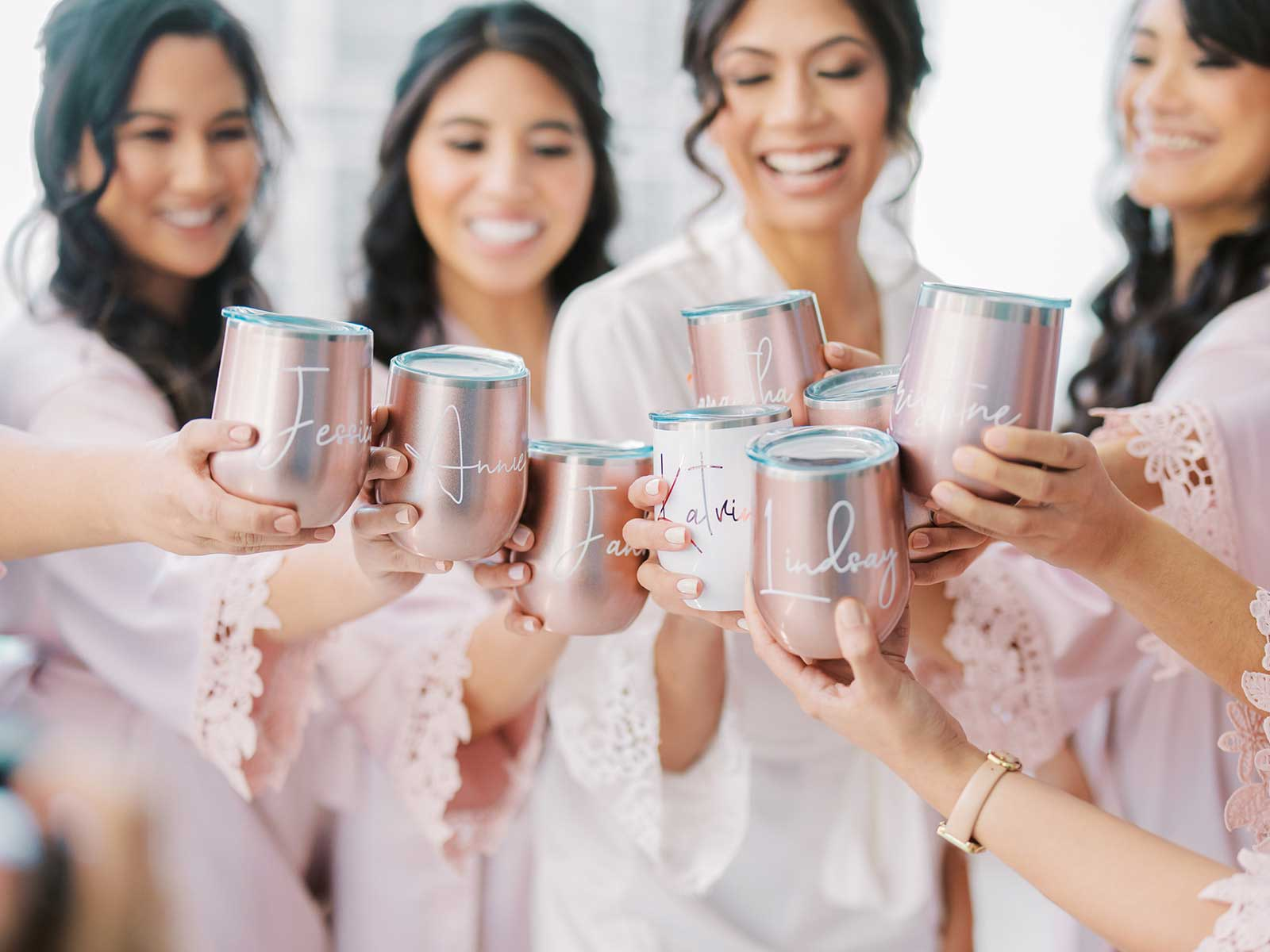 bride and bridesmaids standing on balcony of the Epic with their matching tumblers.