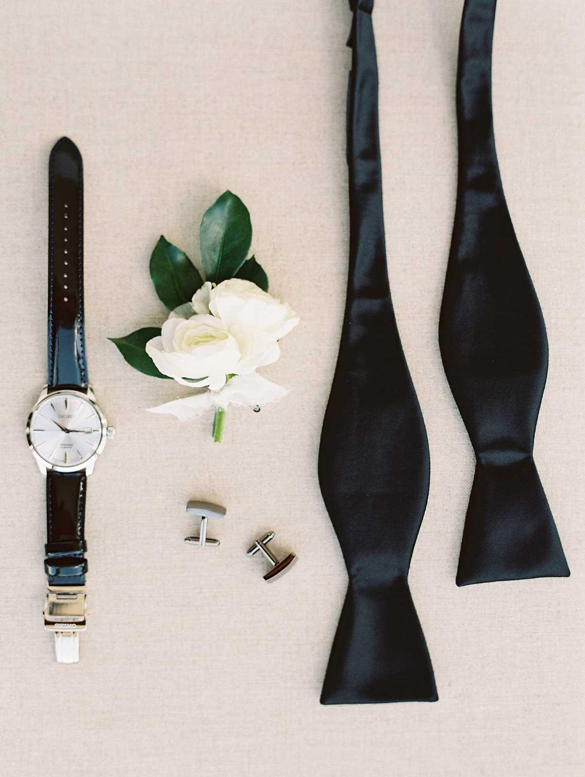 closeup of bowtie, boutonniere, watch and cufflinks.