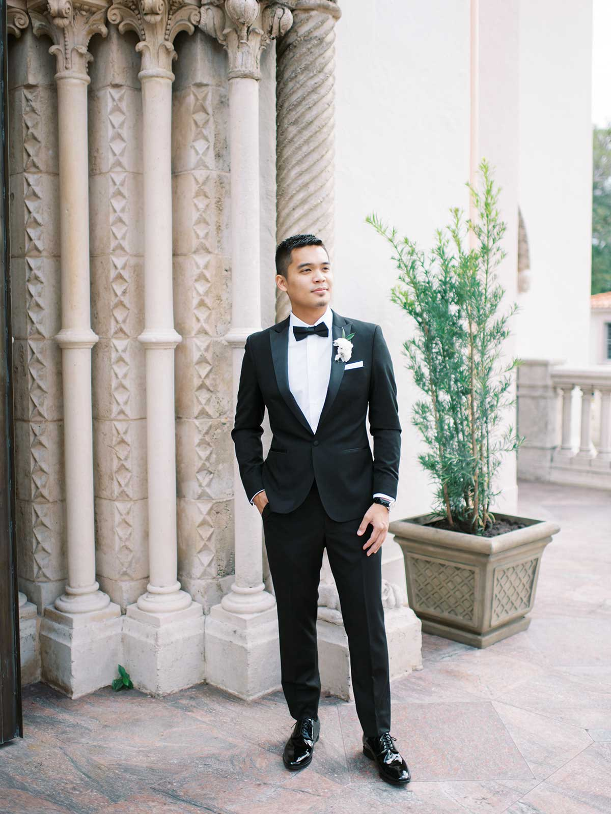 groom poses for photo in his tux and boutonniere.