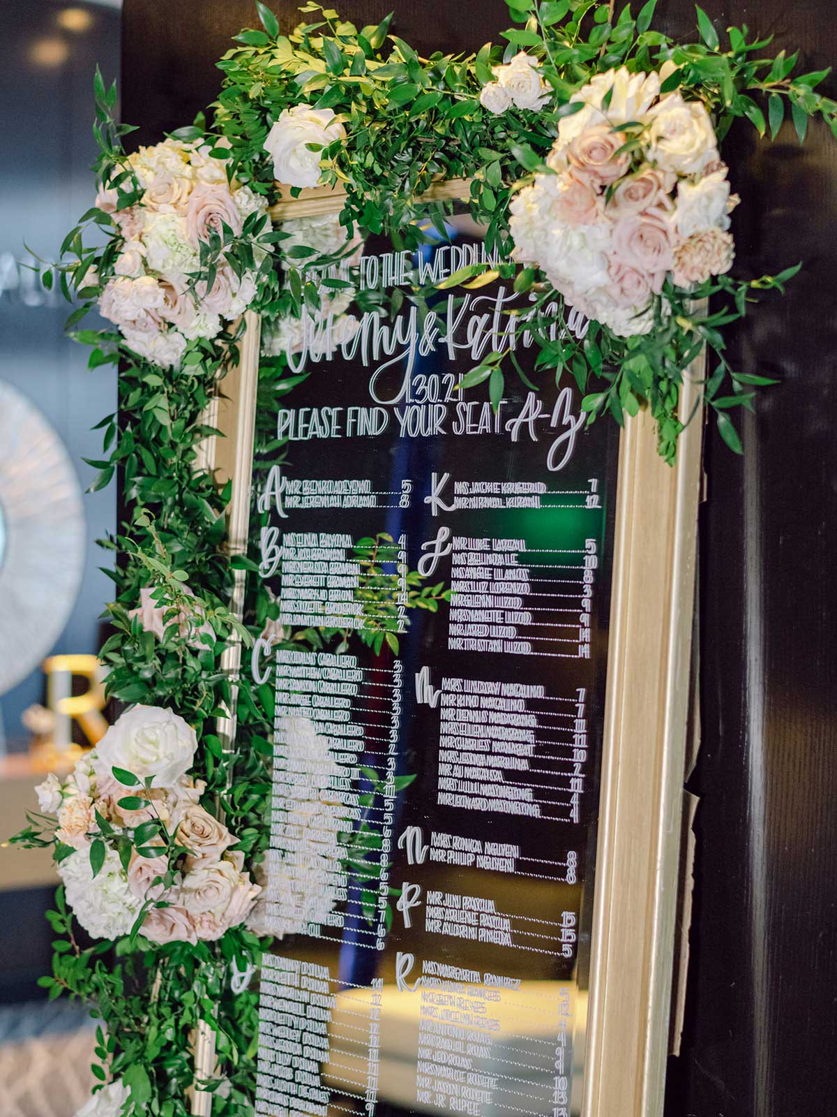 glass seating chart with gold frame and flowers.