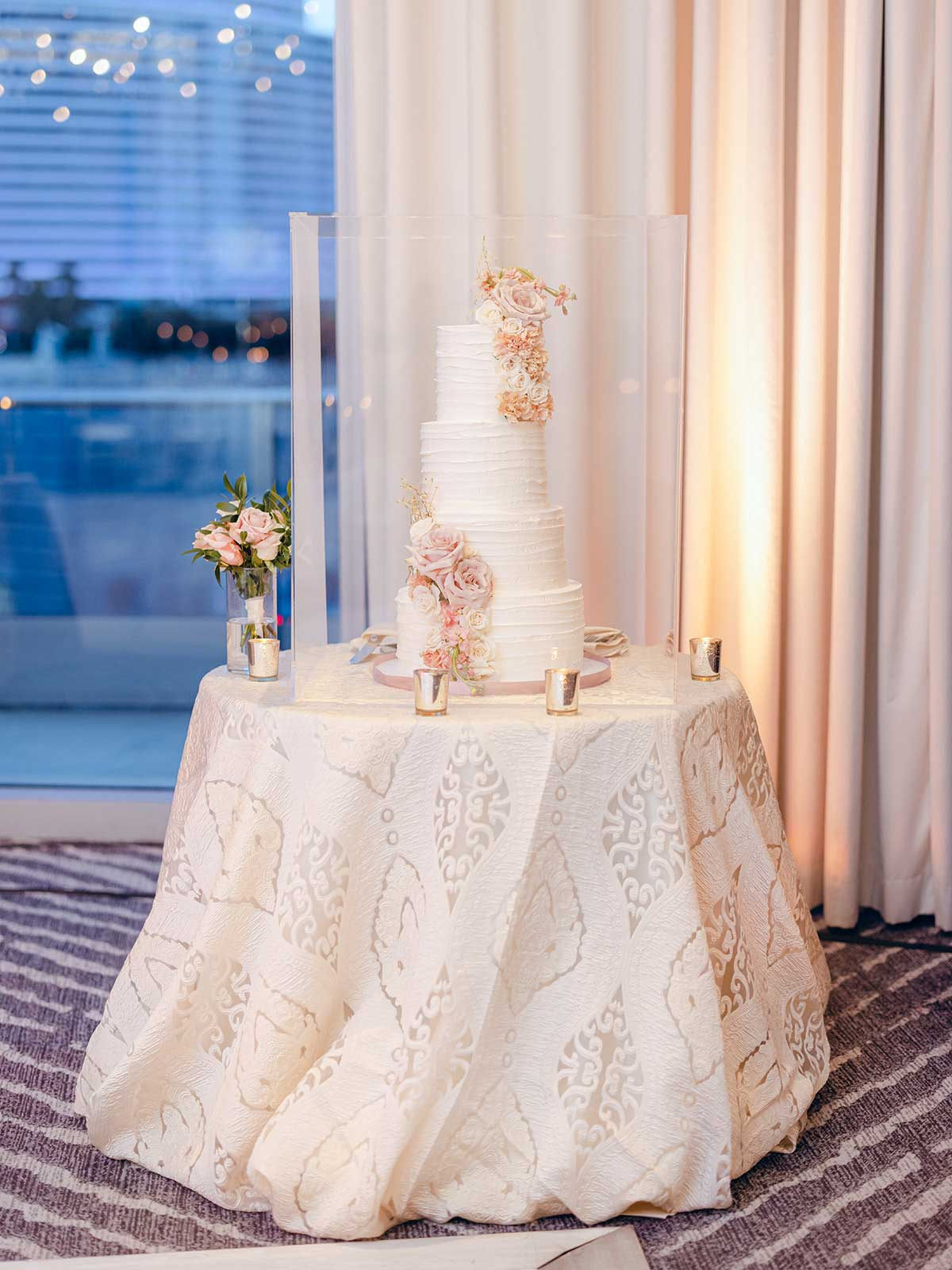 4 tiered white wedding cake with pink flowers draping on the side.