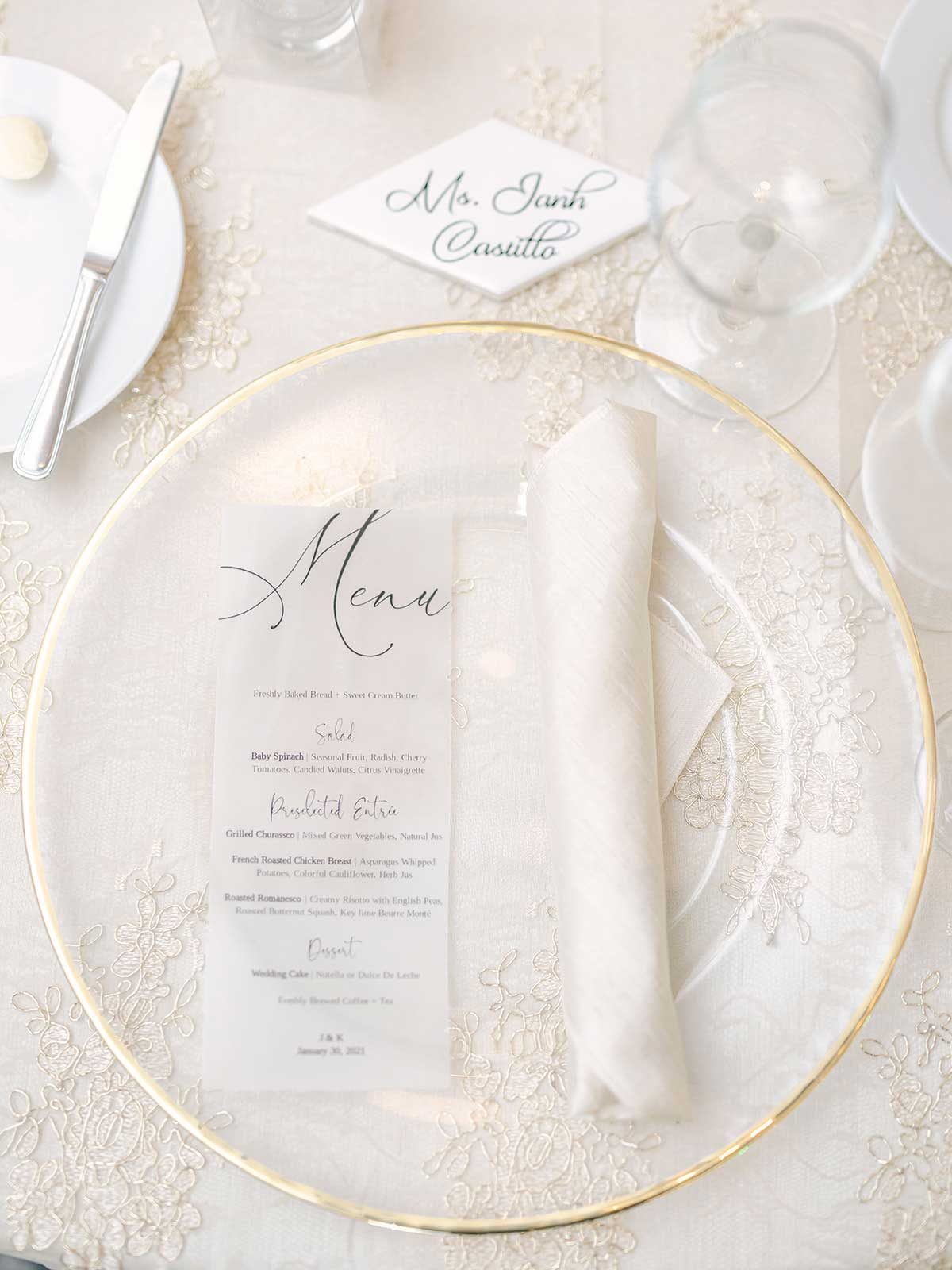 menu, gold rimmed plate and napkin on white lace tablecloth.