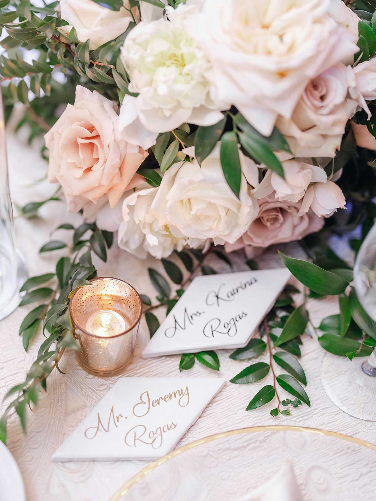 Bride and groom place cards on head table with flowers and candles.