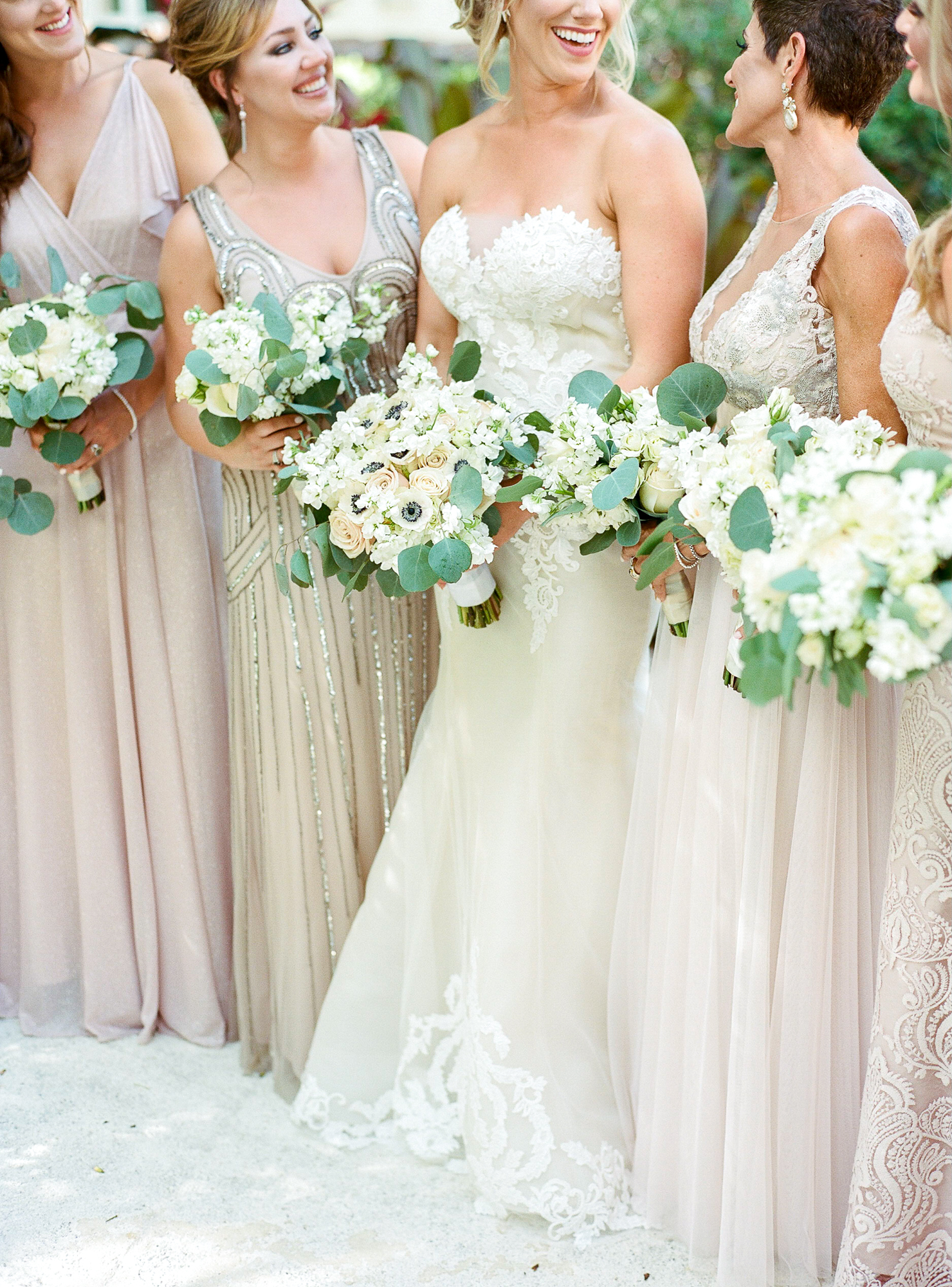 A closeup of the bouquets as the bride and bridal party stand outside and smile at each other.