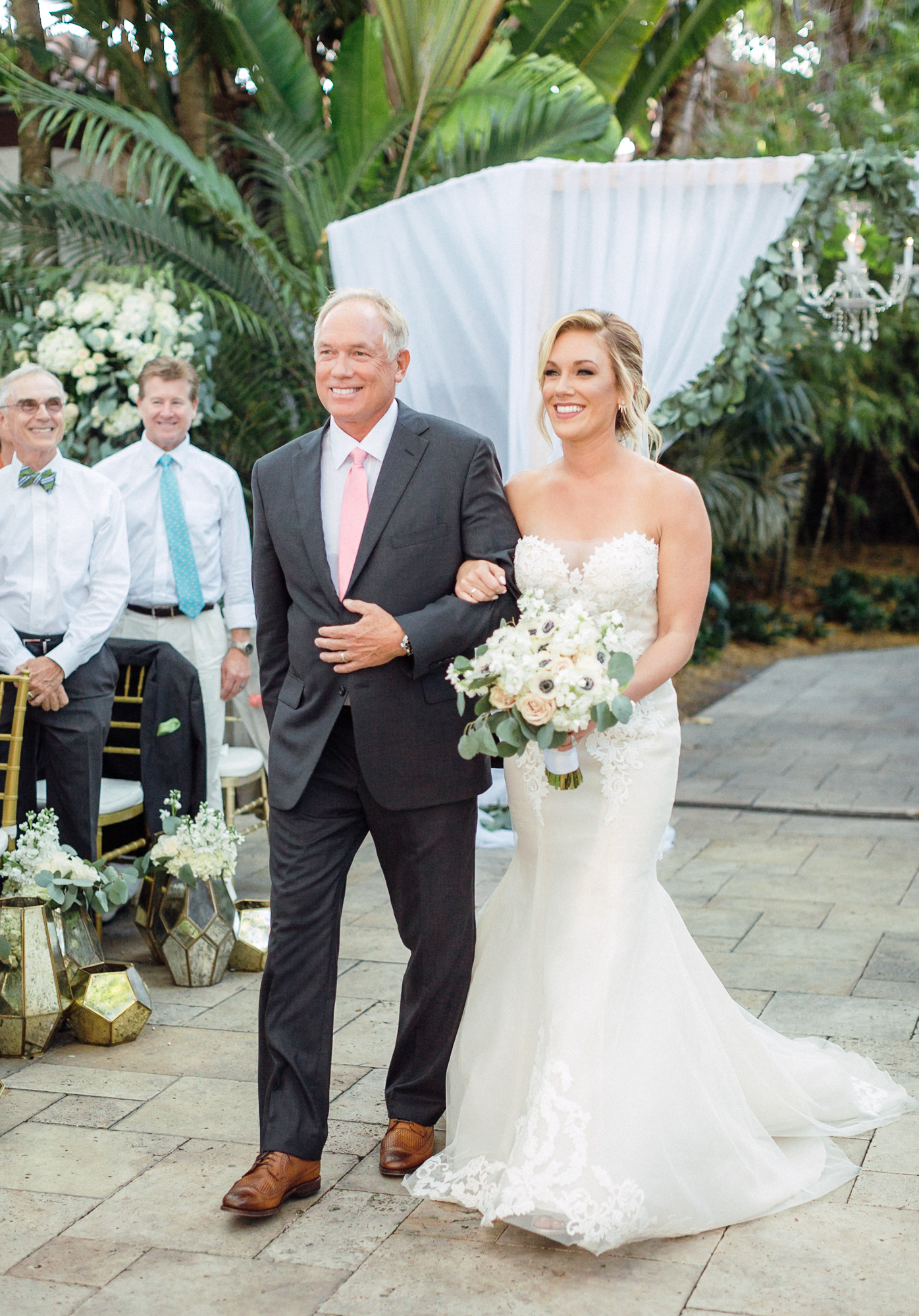 Father of the bride walks his daughter down the aisle in the outdoor ceremony at Fisher Island Club.
