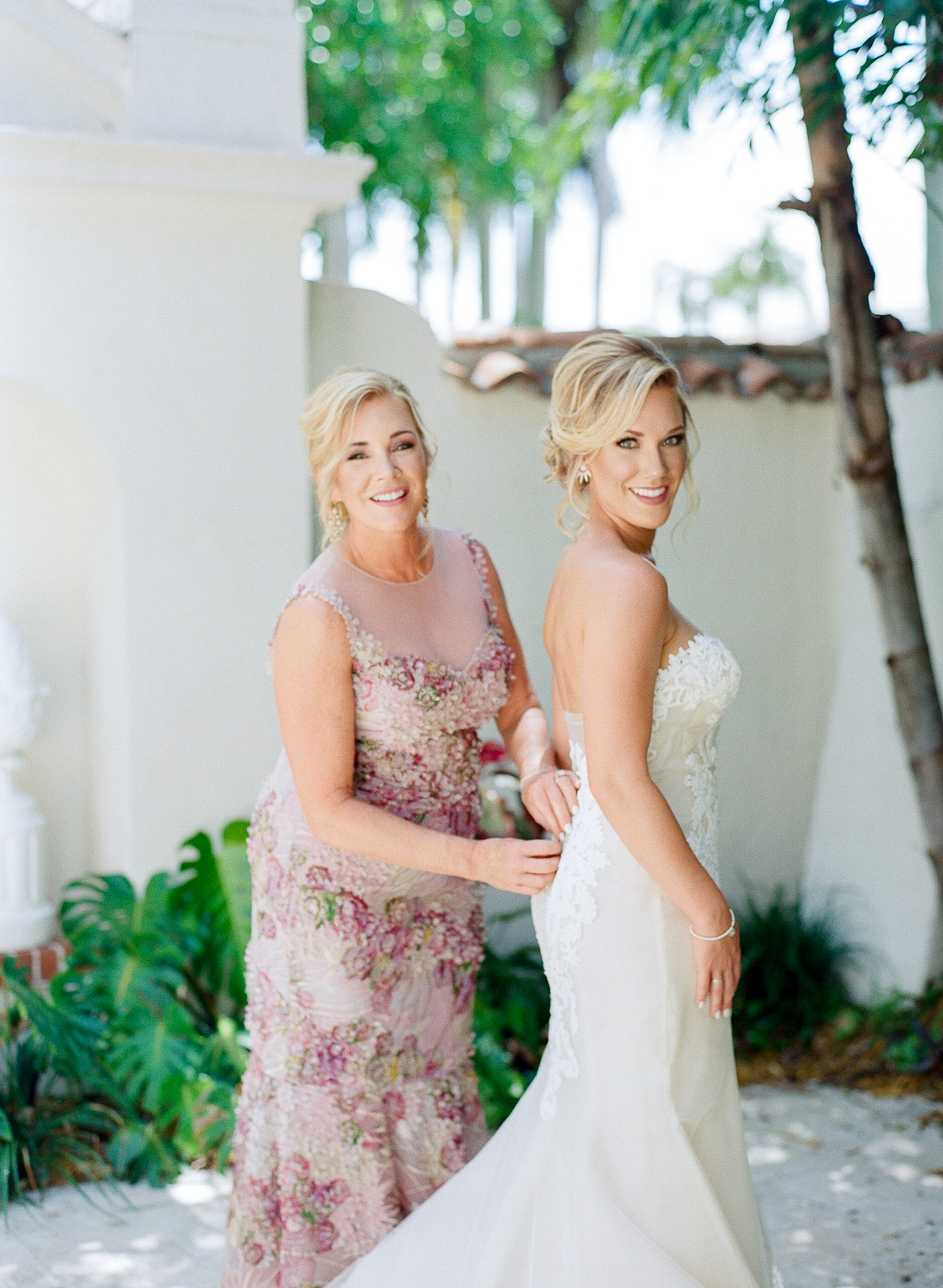 Mother of the bride buttons her daughter's gown outside while both look and smile towards the camera.