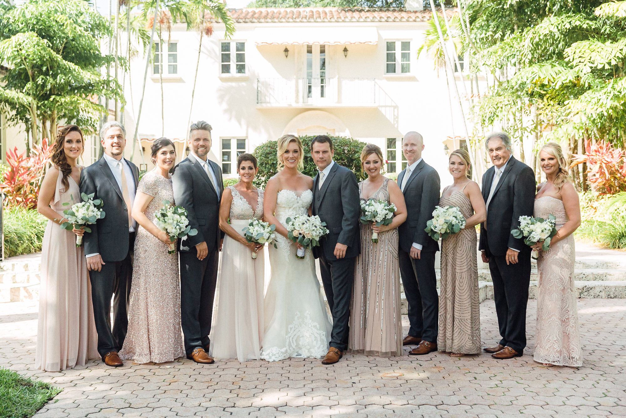 Wedding party stands outside in a straight line with couple in the center.