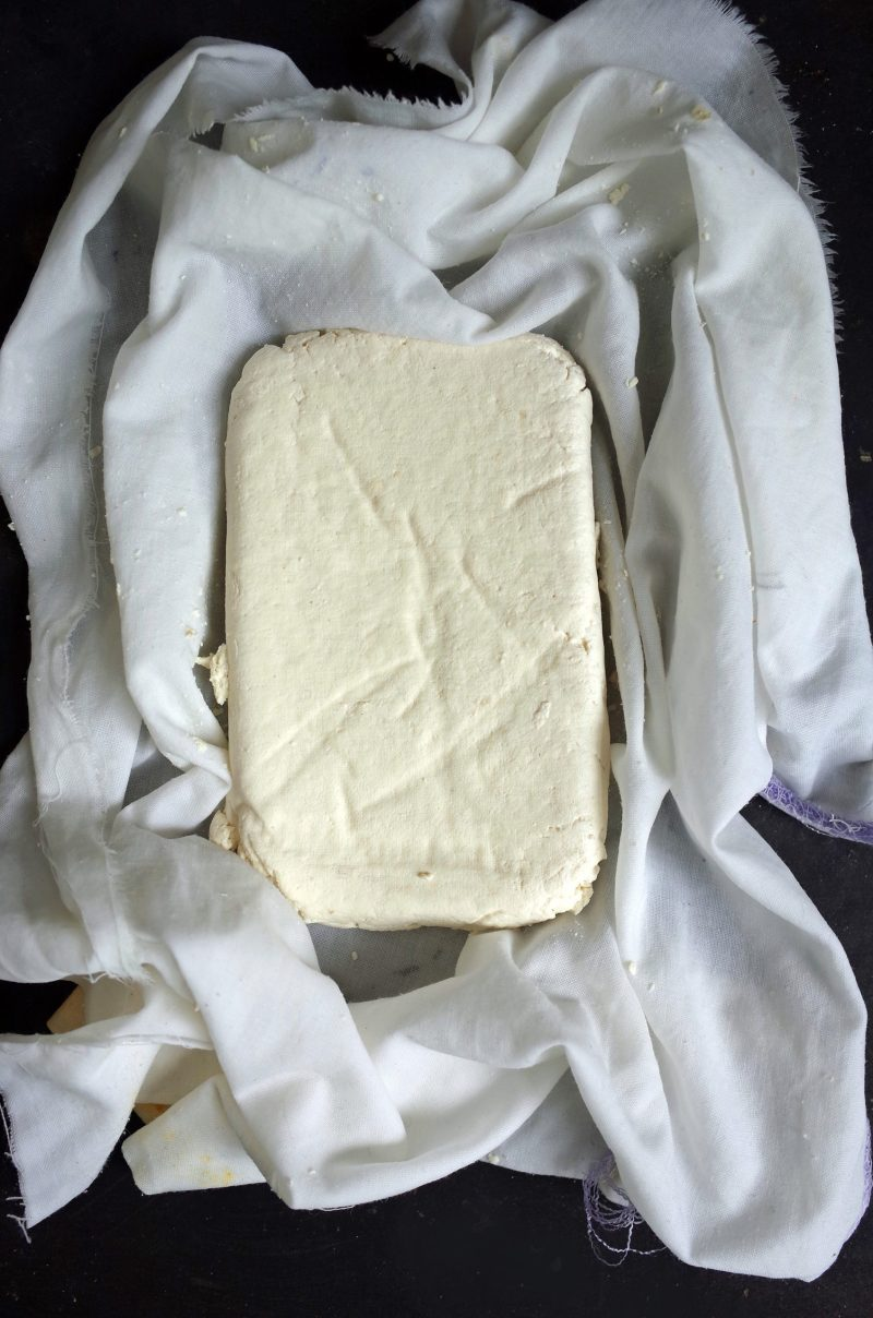 A block of homemade tofu made from soy milk on a cheesecloth