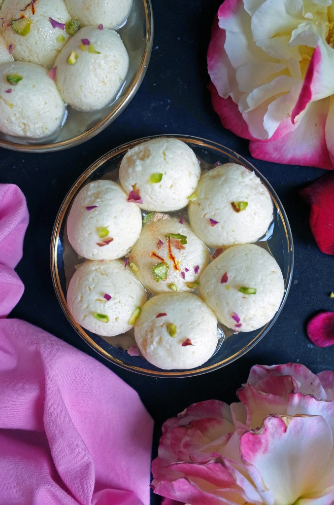 Spongy Bengali Rasgulla topped with Rose, Saffron and Pistachio on a black background with roses and pink cloth