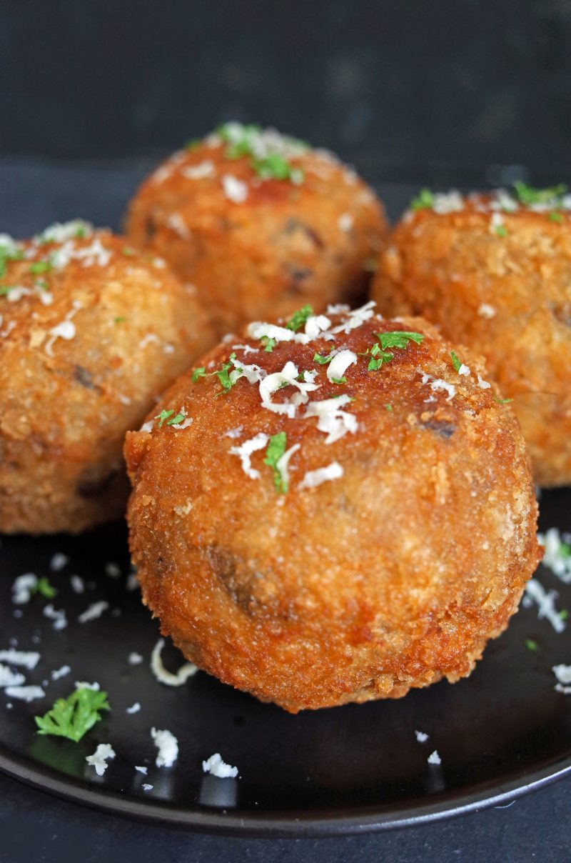 Close up of Oh My Veg crispy Mushroom Arancini on a black plate topped with grated cheese and fresh parsley