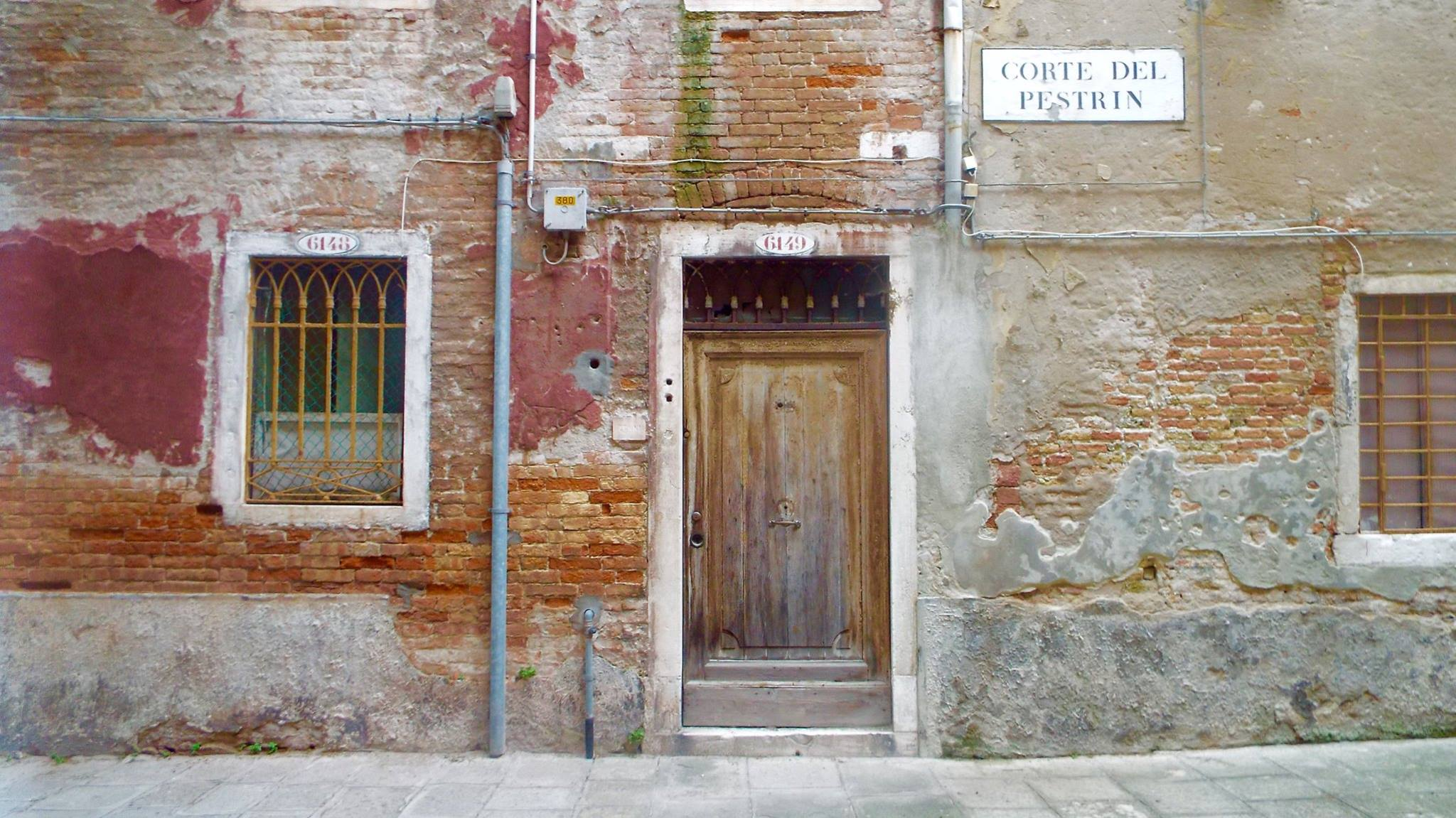 Front facade of an old Italian building with worn out plaster, paint and bricks, a door, window and street sign