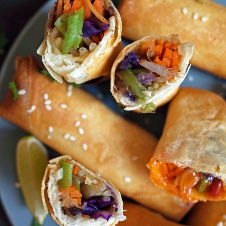 Crispy Vegetable Spring Rolls displayed with sesame seeds, lime and coriander on a blue plate