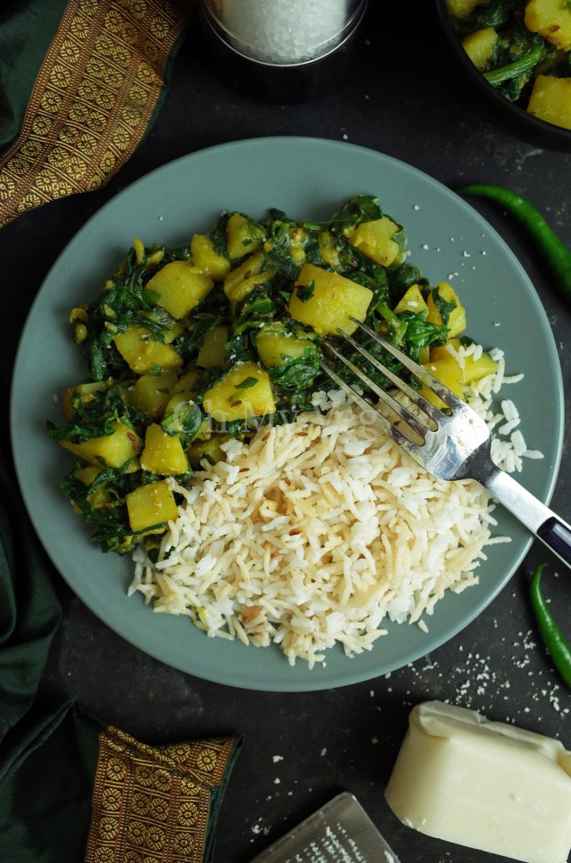 Aloo Palak / Saag Aloo on a blue plate with rice, coconut and a fork