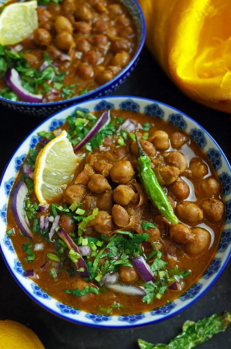 Two bowls of Vegan Chana Masala garnished with green chillis, coriander, onion and lemon slices