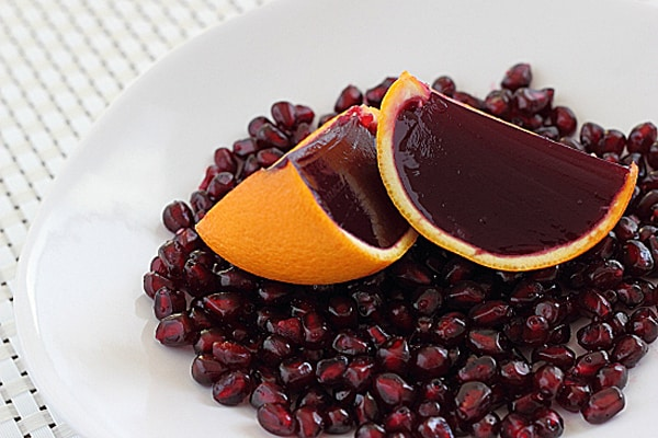 Orange wedges filled with pomegranate flavored gelatin on pomegranate seeds and a white plate