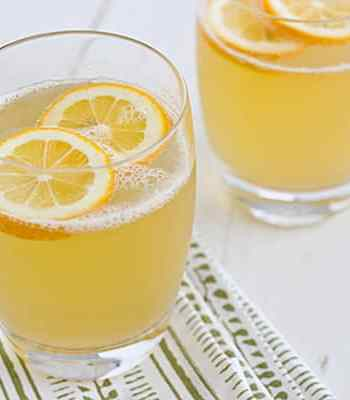 Sparkling Meyer Lemonade in glasses on a white tabletop with lemon wedges floating in them