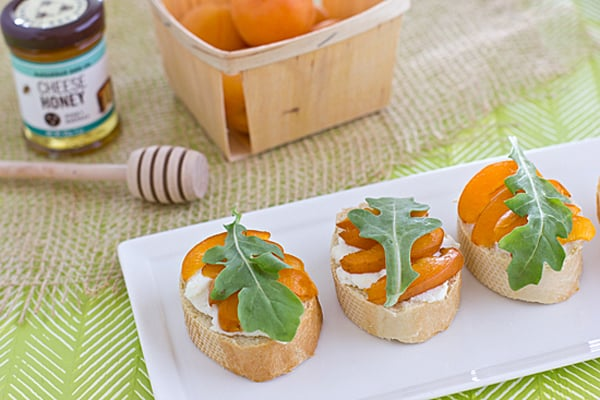 Apricot crostinis on a white plate next to a basket of ripe peaches