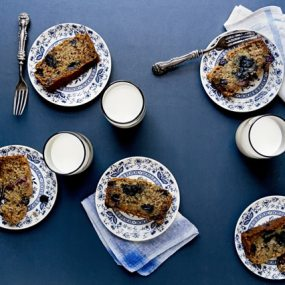 glasses of milk and small blue and white plates of blueberry bread sit on a dark blue table