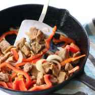 Cooking Seitan in pan with red peppers