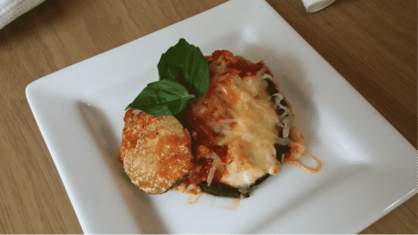 eggplant parmesan on white plate with fresh basil