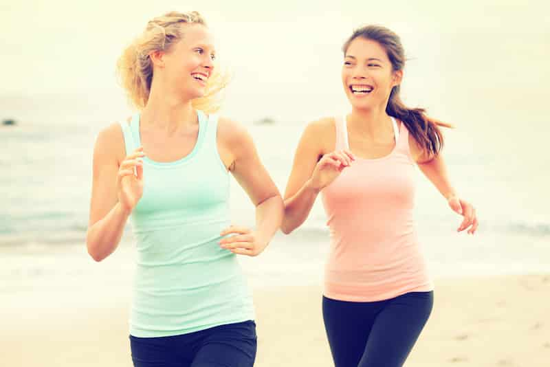 Women running exercising jogging happy on beach training as part of healthy lifestyle. Two fit female runners talking happy and smiling during workout. Multiracial Asian and Caucasian woman.