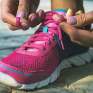 Hands of a young woman lacing bright pink and blue sneakers. Shoes standing on the pavement of stones and sand. In female hands purple-yellow manicure. Photographed close-up.