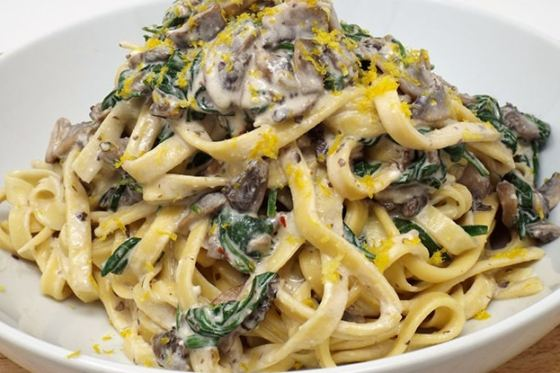 Yellow noodles piled with spinach and mushrooms coated in cream sauce on a white plate