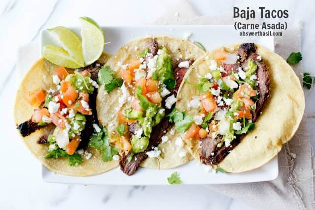 Three authentic carne asada tacos with three slices of lime on a white serving platter.