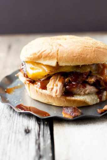 BBQ Rib Sandwiches with crispy bacon and cheddar cheese on a silver serving plate on a wooden table.