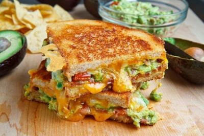 Bacon Guacamole Grilled Cheese Sandwich on a wooden board surrounded by avocados, salsa and chips.