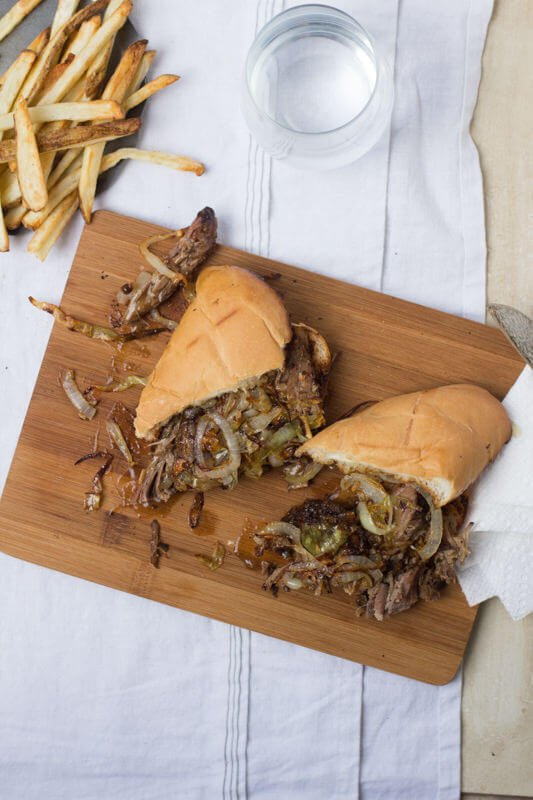 Pot Roast sandwich cut in half on a wooden board on top of a white table cloth next to french fries.