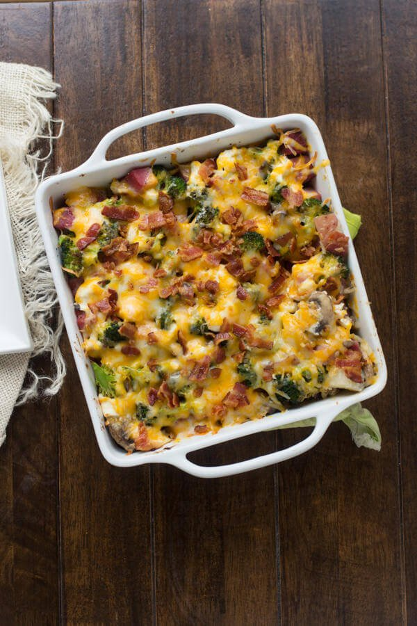 ham and potato casserole topped with cheese and bacon in white baking dish