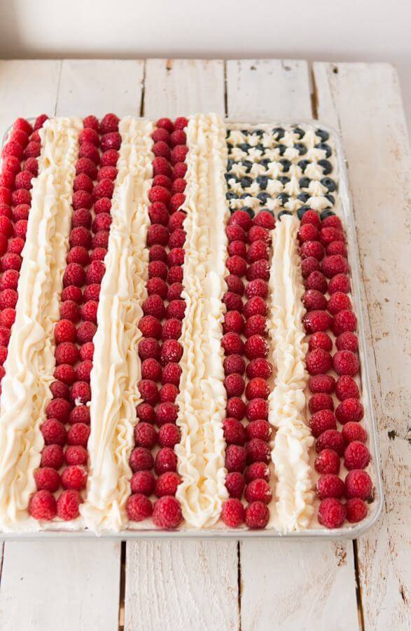 Flag cake, white cake with a light whipped cream frosting, berries and buttercream stripes. Could this flag cake be better than Ina Garten's? I think it might! ohsweetbasil.com 4th of July party food!