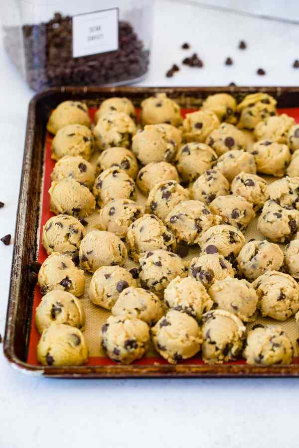 A photo of a sheet pan full of balls of chocolate chip cookie dough.