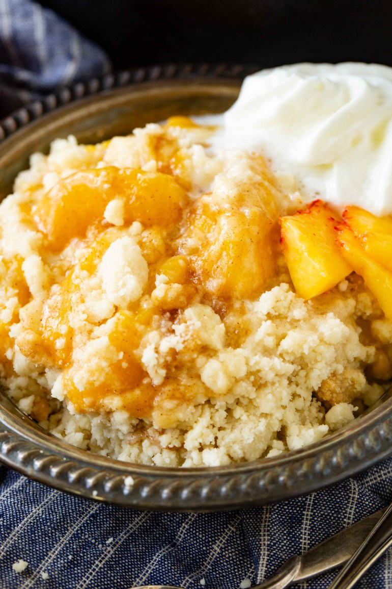 a metal bowl with fresh, juicy peach cobbler and a dollop of whipped cream