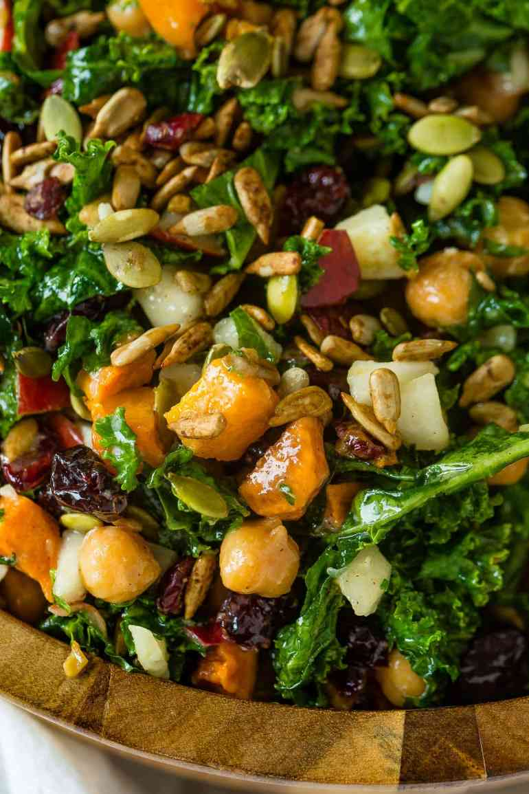 A close up photo of a kale salad topped with roasted butternut squash, craisins, chickpeas, pepitas, and gouda cheese.