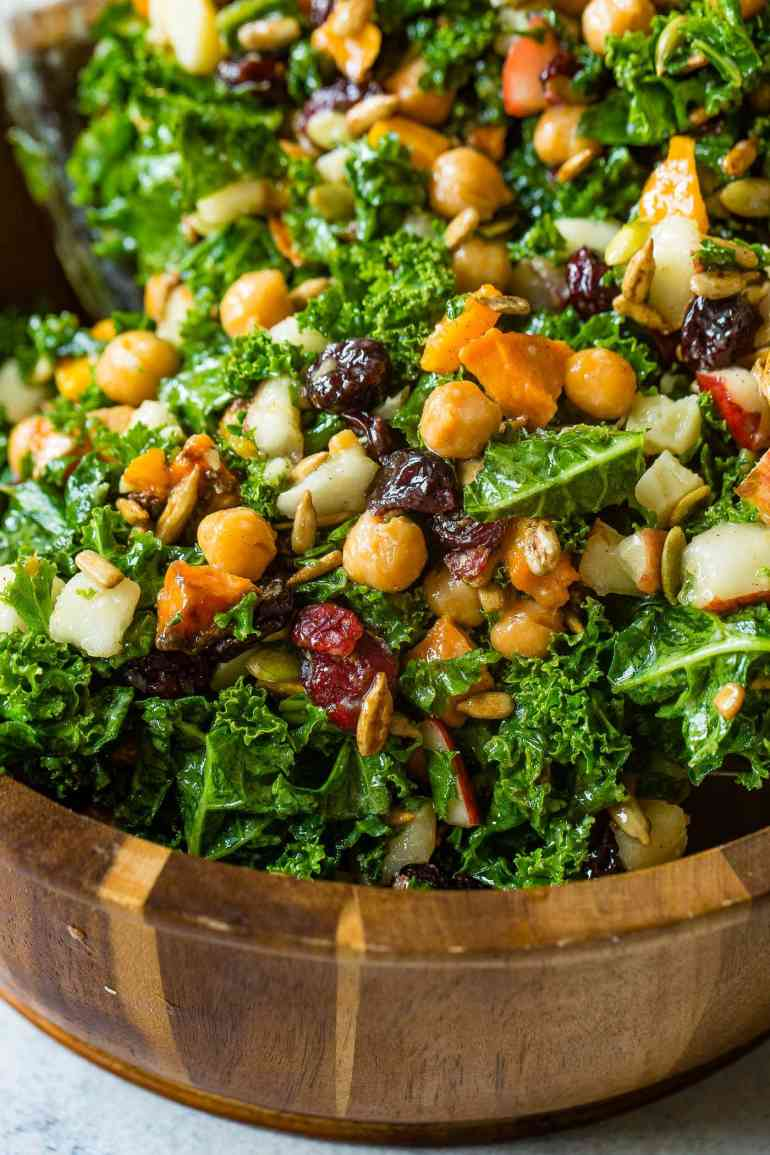 A photo of a large wooden bowl full of kale salad topped with roasted butternut squash, craisins, chickpeas, pepitas, and gouda cheese.