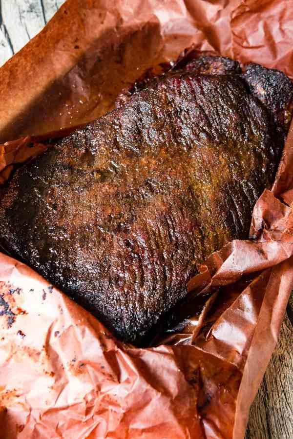 A photo of a perfectly smoked brisket with a delicious crusty bark sitting in peach butcher paper.