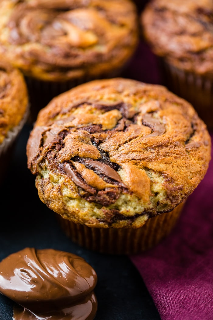 A close up photograph of a nutella swirled banana muffin with more muffins in the background