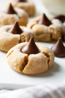 A photo of several peanut butter blossom cookies with one in the forefront and a hershey kiss sitting next to it.