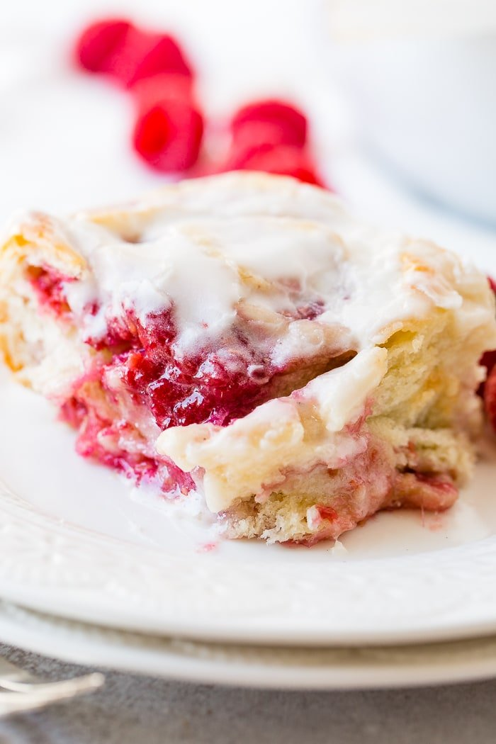 A photo of a easy raspberry sweet roll sitting on a white plate and covered in frosting.