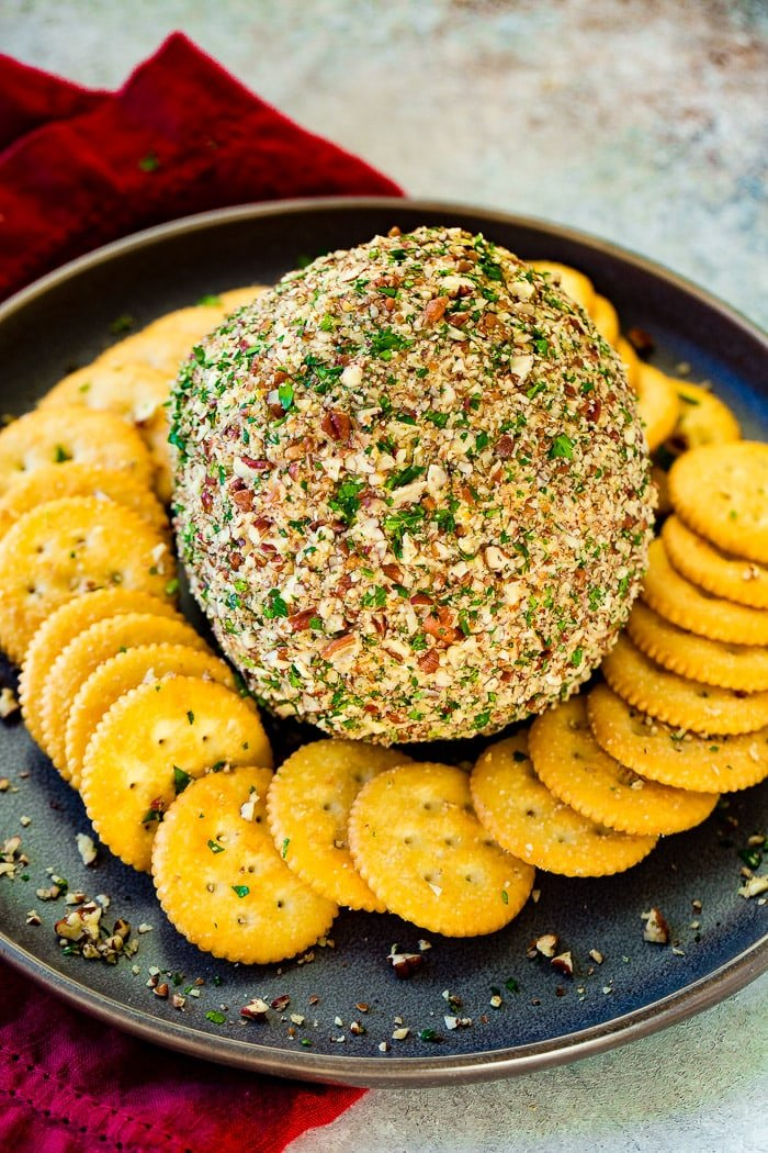an overhead photo of a cheese ball rolled in chopped pecans and parsley with ritz crackers surrounding it.